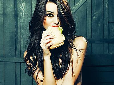 A naked girl eating a sandwich
