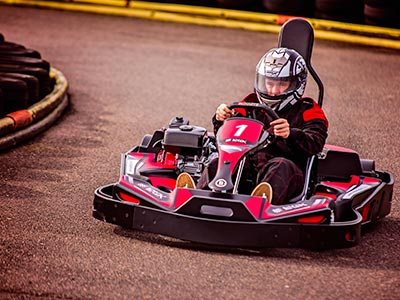 Three people driving karts on an outdoor track