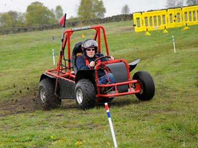 A yellow rage buggy in a field
