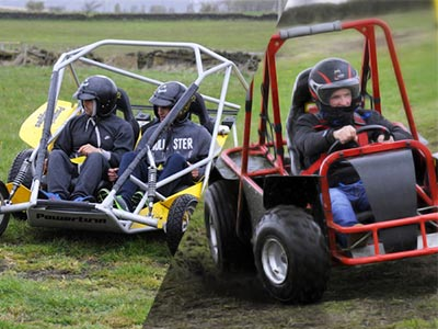 Two men in a yellow rage buggie, steering through a field