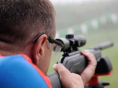 Over the shoulder shot of a man aiming with a rifle outdoors