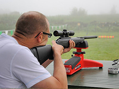 A man in a white shirt aiming with a rifle outdoors