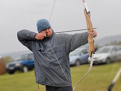 A side view of a man firing an arrow