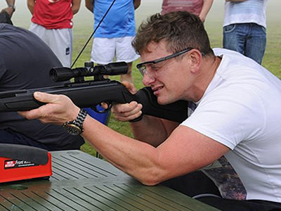 A man in a white shirt crouching down and aiming with an air rifle