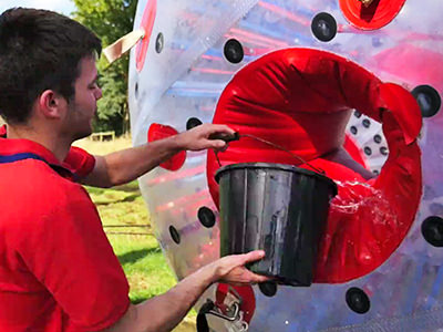 A man in a red shirt pouring water from a silver bucket into a zorb