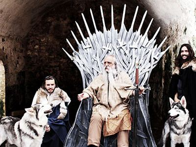 A man in costume sat on the Iron Throne from Game of Thrones, with two people and a husky sat next to him
