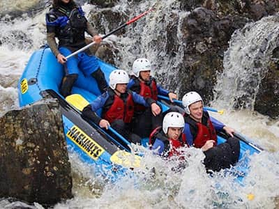 A bird's eye view of a white water rafting raft paddling through rapids