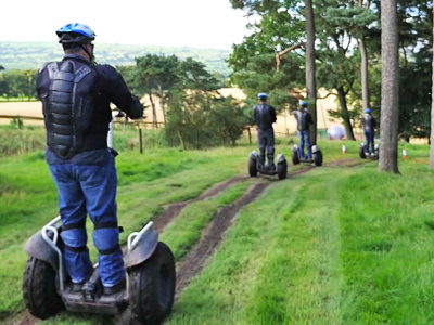 People driving segways into a forest