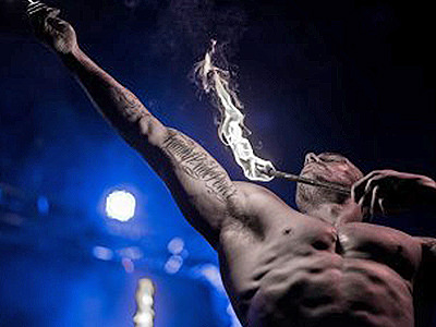 A close up of a semi-naked man playing with fire