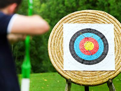A man aiming a bow and arrow at a target outdoors