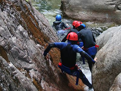 Some men climbing down some rocks and heading to the river