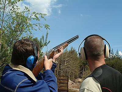 A man shooting a gun into the sky with another man helping