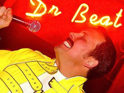 A man dressed as Freddie Mercury singing into a microphone