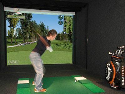 A man swinging a golf club in a virtual golf booth