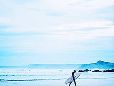 A man holding a surfboard, walking along the beach