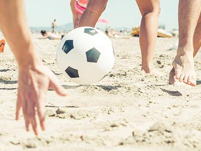 A ball bouncing on the beach with people's hands near it