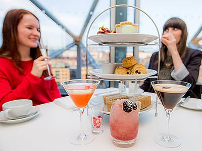Three cocktails and a cake stand, with two women in the background