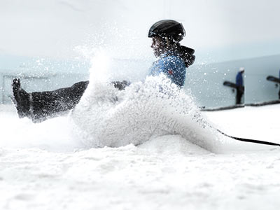 Close up of a person's feet on a snowboard in the snow