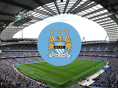 Man City logo on top of an image of the pitch at Etihad Stadium