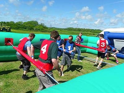 Men in an inflatable and strapped to ropes as they play human table football