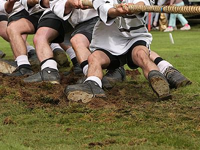 Close up of men's legs in the mud as they play tug of war