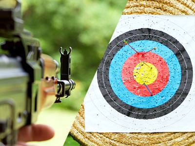 A split image of the view down the side of a Kalashnikov-style rifle and a wicker target with arrows in it