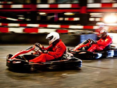 Two go karts whizzing around a track with people in red overalls driving