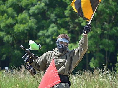 A man holding up a black and yellow flag whilst also holding a paintball gun in a field
