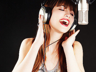 A woman singing into a microphone with headphones on