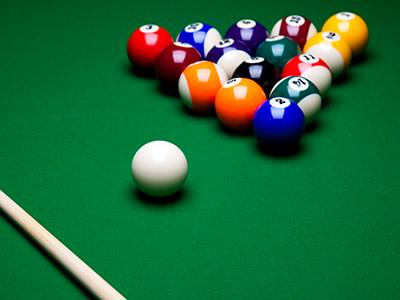 A 'racked' set of pool balls, a cue ball and a cue on a green pool table