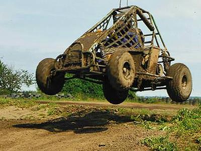 An off-road buggy going over a jump on a dirt track