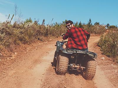 The back of a man in a red and black checked shirt, driving a quad bike down a dirt path