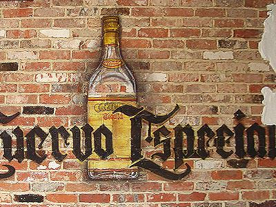A mural on a brick wall of a bottle and some Spanish writing