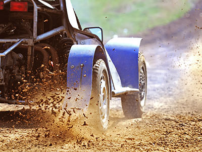 A rage buggy's wheels driving through mud