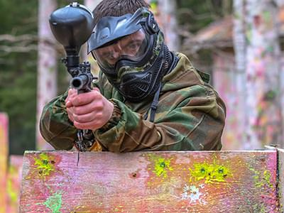A man hiding behind a barrier, firing a paintball gun