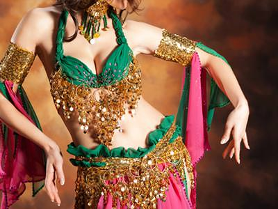 A close up of a woman's torso and lower body in a green and gold sari top and skirt, holding her arms aloft