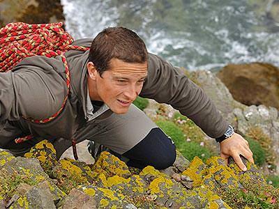 Bear Grylls climbing a sheer rockface