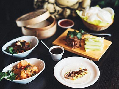 Multiple small plates of Asian food