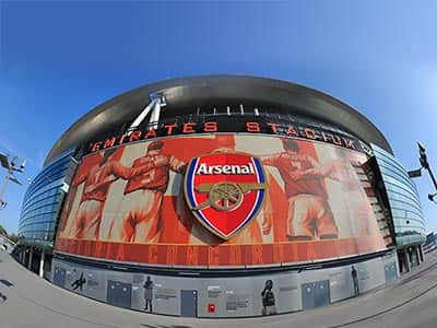 Arsenal badge on top of a blurred image of the inside of Emirates Stadium