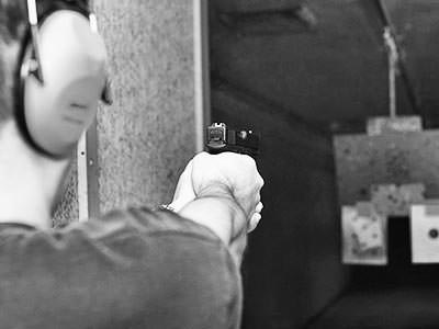 blakc and white image of man with hand gun at an indoor shooting range