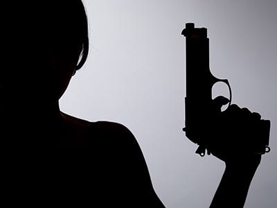 A silhouette of a woman holding a gun to the air