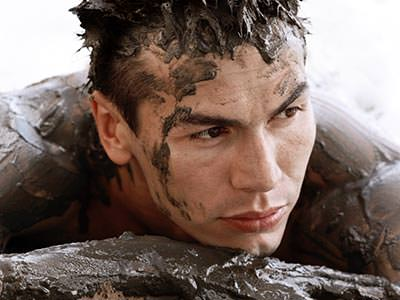 A close up of a man's face and top of body, covered in mud
