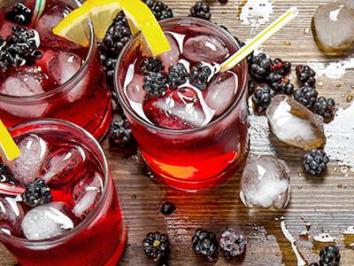 Three red drinks topped with ice and blueberries on a table, alongside ice cubes and blueberries