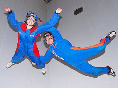 Two people in blue jumpsuits floating in the air in a skydiving simulator