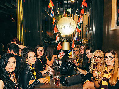 Close up of women sat at a table in Harry Potter costumes, and posing for the camera