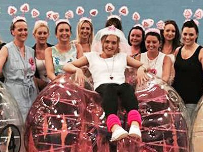 A close up of a woman sat in a pink zorb, wearing a veil, with woman stood around her in hen party headboppers