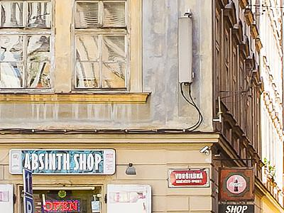Close up of a sign saying Absinth Shop on the side of a wall