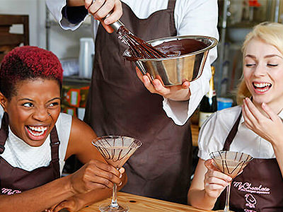 Two women drink chocolate cocktails, whilst someone in the background whisks chocolate in a metal bowl