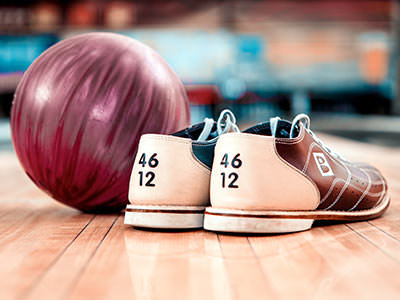 A bowling ball and some bowling shoes lying next to each other in a bowling alley