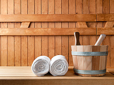 Two white rolled up towels next to a wooden bucket, inside a sauna